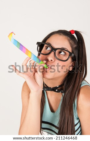 Cute nerdy girl blowing  a party horn. Studio shot.