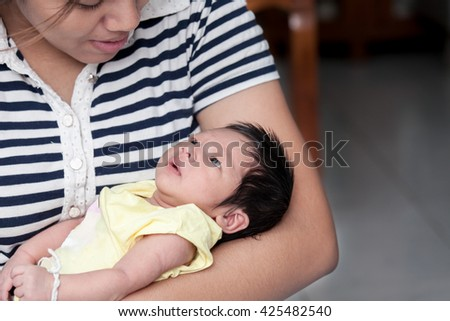 Cute newborn baby boy is lying on mother arm  in vintage color tone - stock photo