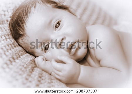 Cute newborn baby boy posing for camera in black & White