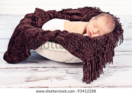 Cute newborn baby boy sleeping in Bowl with blanket - stock photo