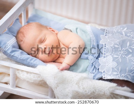Cute newborn baby boy sleeps in a small bed - stock photo