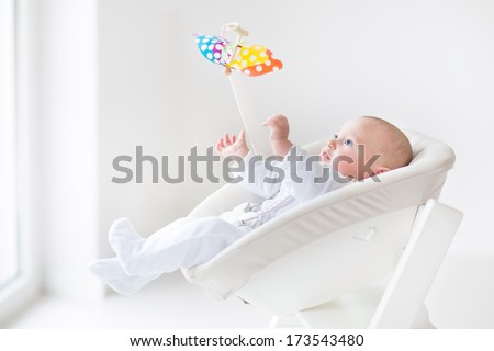 Cute newborn baby boy watching a colorful mobile toy sitting in a white high chair next to a window - stock photo