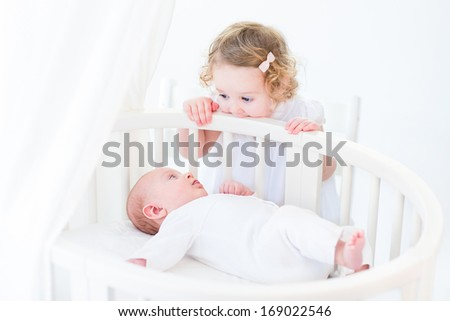 Cute newborn baby boy watching his toddler sister standing at his white round crib in a sunny bedroom