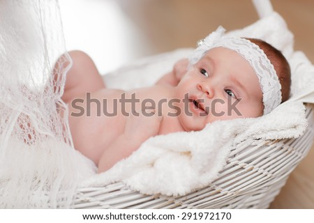 Cute newborn baby girl sleeping in basket, little girl new born baby smiling, portrait of 1 month baby girl, adorable kid in cozy accessories at home, soft focus, mother care concept, series - stock photo