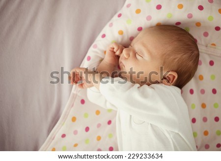 Cute newborn baby girl sleeping in bed at home - stock photo