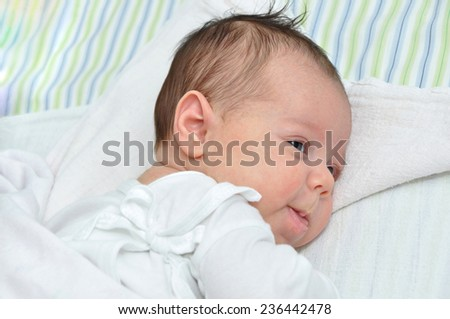 Cute newborn baby girl smiling and lying in bed - stock photo