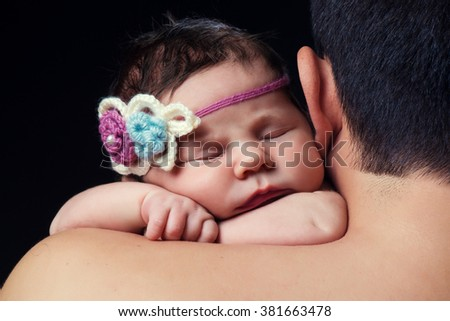 Cute newborn baby girl with knitted headband sleeping on dad's shoulder.  Studio, black background