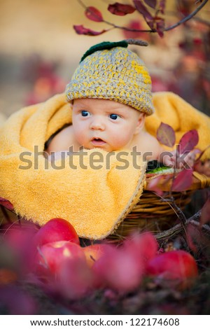 Cute newborn baby in a funny knitted hat in basket with apples - stock photo