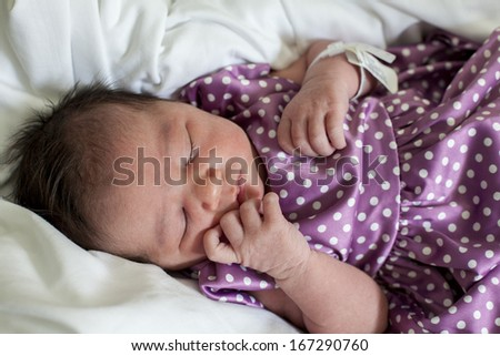 Cute Newborn Baby in Purple Polka dot dress - stock photo