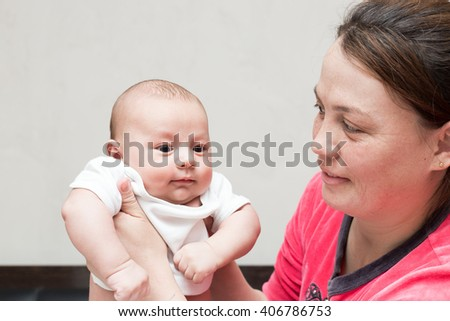 cute newborn baby is holding mother