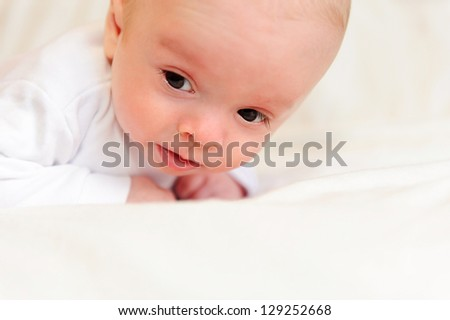Cute newborn baby lying in bed. Close-up view. - stock photo