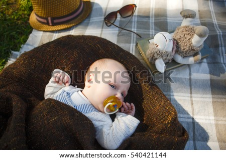 cute newborn baby Lying on the carpet in the grass. Picnic in the park. Enjoying motherhood,happy family concept. Nature on background.