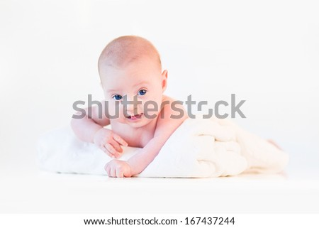 Cute newborn baby relaxing on his tummy on a white soft blanket