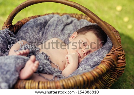 Cute newborn baby sleeping in basket outdoor - stock photo