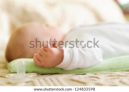 Cute newborn baby sleeping in bed. Shallow depth of field. - stock photo