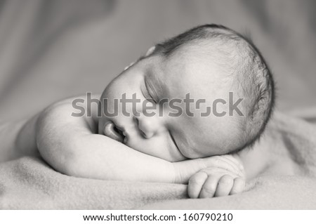 Cute  newborn  baby sleeping  on a  blanket ( black and white ) - stock photo