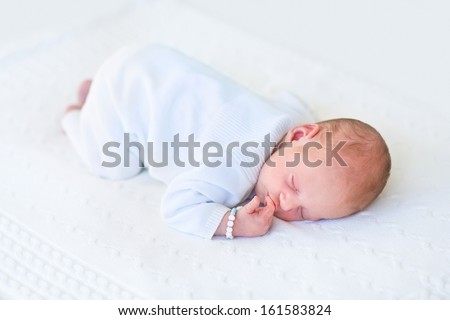 Cute newborn baby sleeping on his tummy on a white knitted blank - stock photo