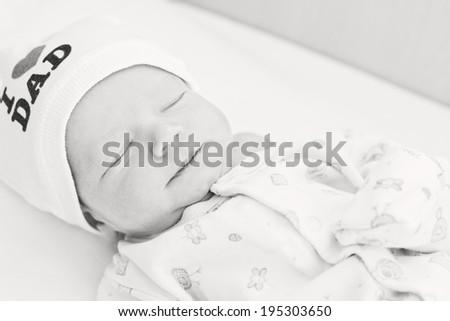 cute newborn baby sleeping wearing hat (not a trademark) (black-white) - stock photo