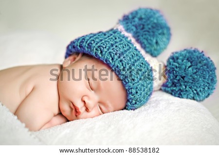 Cute newborn baby sleeps in a hat - stock photo