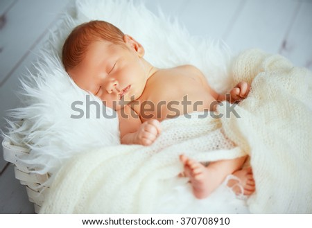Cute newborn baby sleeps in white basket - stock photo