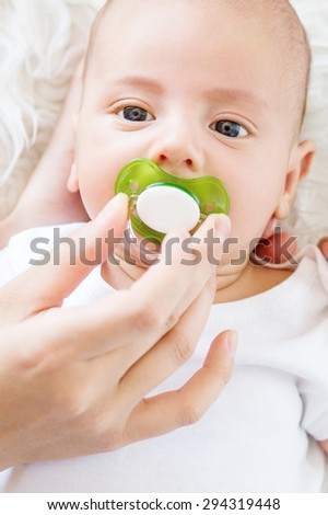 Cute newborn baby with a pacifier on a white background