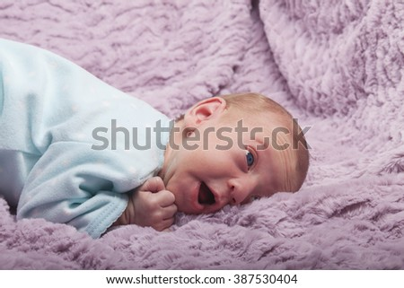 Cute newborn baby with cheerful expression on soft pink blanket - stock photo