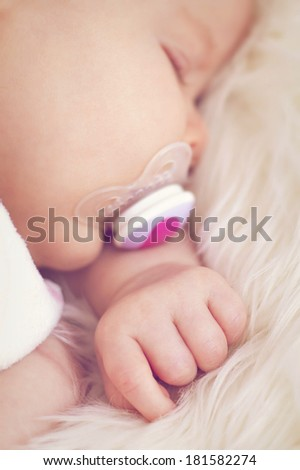 Cute newborn girl is sleeping on the fluffy blanket