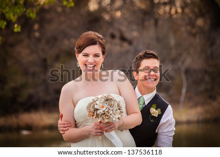 Cute newlywed gay couple laughing together - stock photo