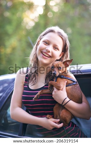 Cute nice happy teen girl with her puppy in car - stock photo