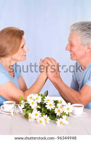 cute old couple at table on blue - stock photo