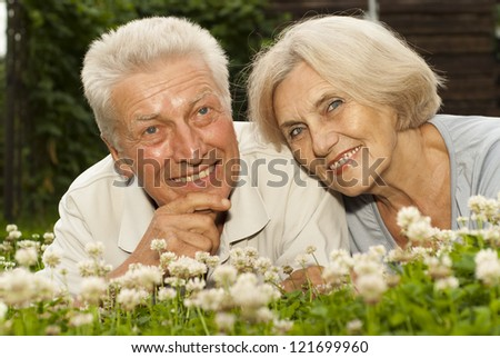 Cute old couple in the middle of the lawn with white flowers - stock photo