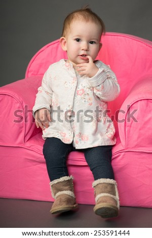 Cute one and a half year old girl sitting on pink chair - stock photo