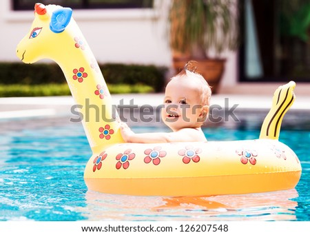 cute one year old baby swimming with a float in the swimming pool - stock photo