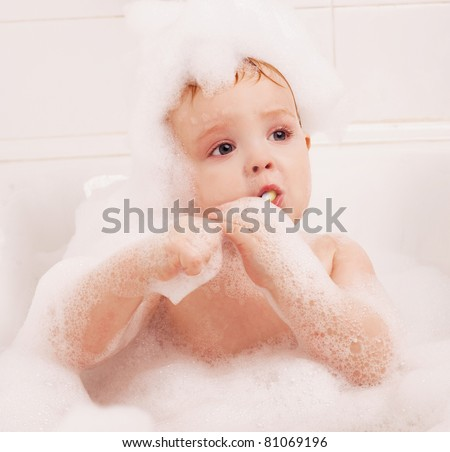 cute one year old baby taking a bath with foam and brushing teeth
