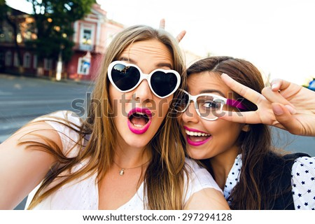 Cute outdoor portrait of funny pretty best friends girls having fun making selfie at city center, positive crazy emotions, traveling together in Europe, joy, vintage glasses, bright make up. - stock photo