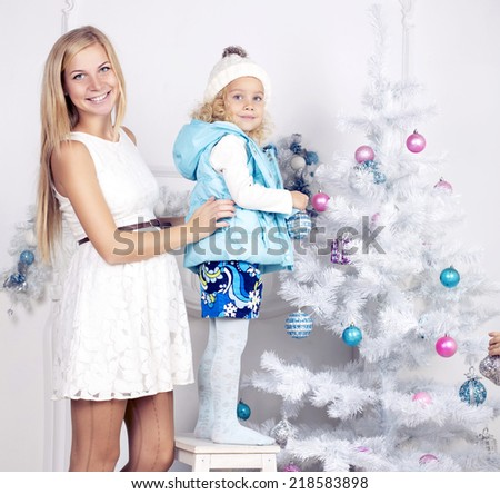 cute photo of little girl with blond curly hair and her pregnant mother decorating Christmas tree - stock photo