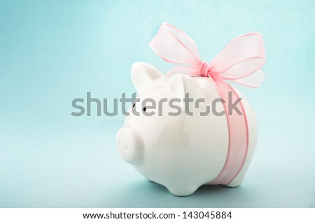 Cute piggy bank with pink bow and ribbon. Side view - stock photo