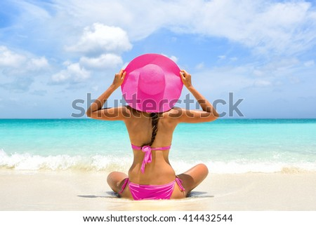 Cute pink bikini beachwear woman relaxing in perfect paradise destination on beach travel vacation. Girl from the back holding fashion straw floppy hat sitting on sand looking a turquoise ocean. - stock photo
