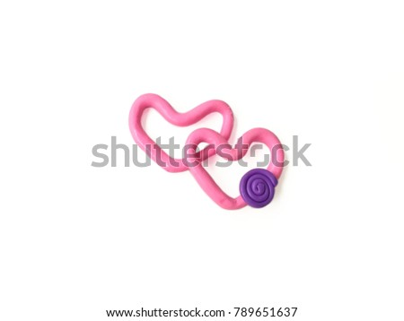 Cute pink heart shape made from plasticine clay on white background, sweetie color dough