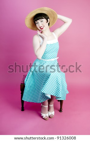 Cute pinup model wearing straw hat and polka dot dress - stock photo