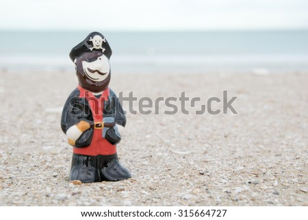 cute pirate ceramic doll on beach