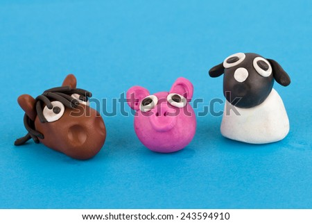 Cute plasticine farm animals collection isolated on blue background. Pig, horse, sheep. - stock photo