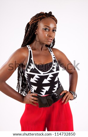 Cute, playful black woman wearing red slacks, standing and looking down and smiling, with her hands on her hips - stock photo