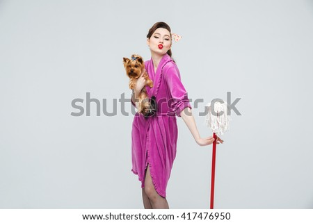 Cute playful young housewife with dog holding mop and sending a kiss - stock photo