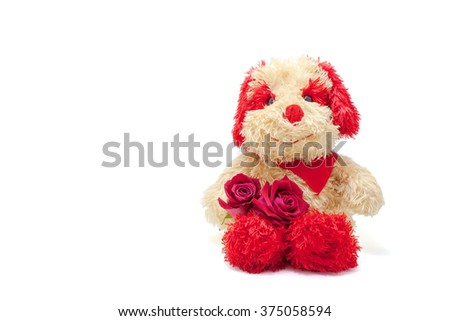 Cute plush toy dog with two red rose and scarf, isolated on white background.
