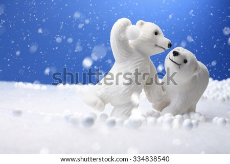 Cute Polar Bear toys on winter snow background.