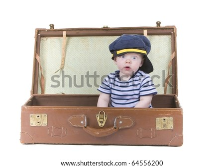 Cute policeman baby sits in suitcase - stock photo
