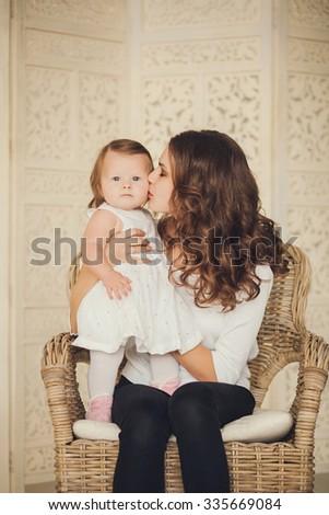 cute portrait of mother kissing her daughter indoor - stock photo