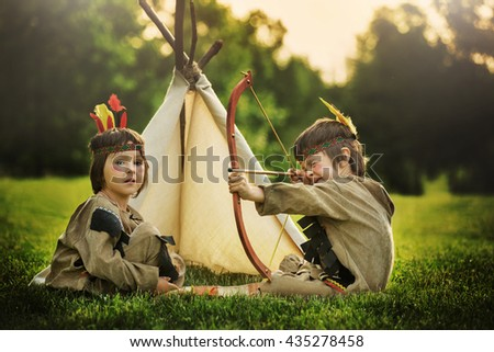Cute portrait of native american boys with costumes, playing outdoor in the park with bow, arrows and hatchet on sunset, summertime - stock photo
