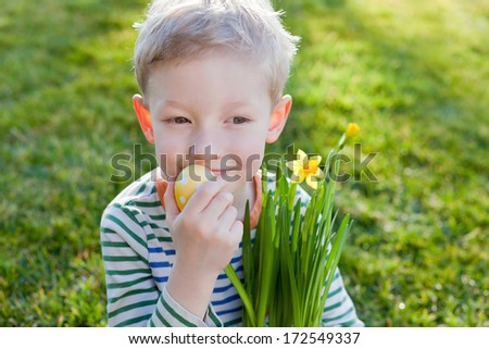 cute positive little boy holding colorful egg and pot with blooming daffodils at easter time